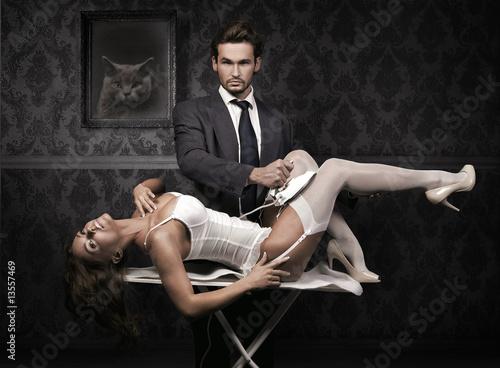 Nowoczesny obraz na płótnie Handsome man ironing attractive brunette