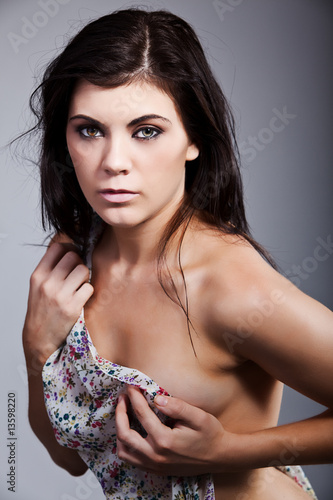 Photo  Attractive brunette holding clothes over her body