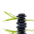 stack black stones with bamboo leaf with reflection