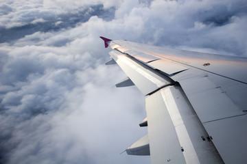 Wschód słońca odbijał się na skrzydle samolotu, wysoko na niebie, nad chmurami