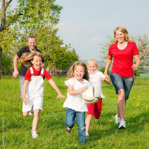 Fotografie, Obraz  Familie spielt Ball auf einer Wiese