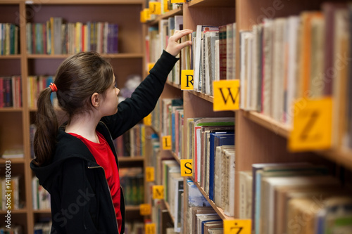 Fotografie, Obraz  Young girl in library looking for books
