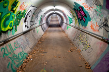 A Long Pedestrian Tunnel Covered With Graffiti And Neon Lights
