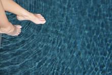 Woman's Feet In A Swimming Pool