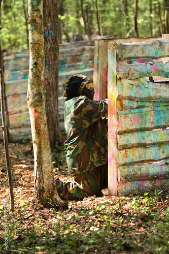 Photo  Paintball gamer, soldier aiming and shooting from barier