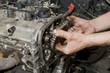 Repairing of diesel engine, close up of worker hands