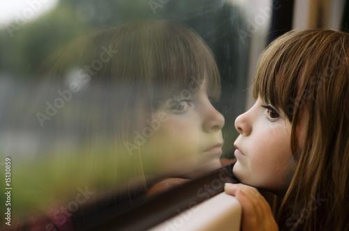 Valokuva  Little girl looking through window