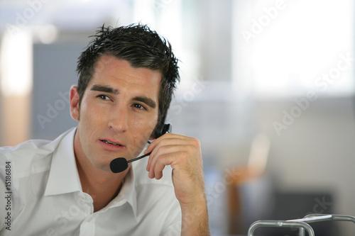 Portrait d'un homme assis à un bureau avec un micro-casque