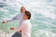 Couple de seniors souriants en courant au bord de la plage