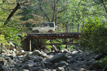 Car Crossing The Bridge In The Summer Forest.