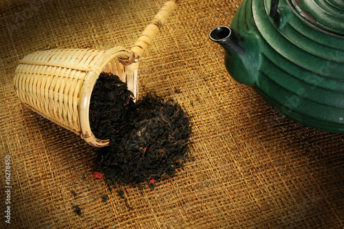 Valokuva  Chinese teapot and a wicker scoop with herb tea leaves