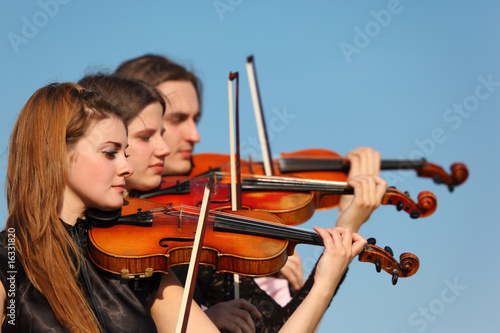 Fotografering  trio of violinists plays against sky