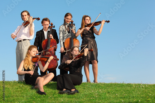 group of violinists play on grass against sky - Buy this stock photo