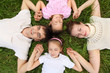 Parents with children lying on grass, view from top, head to hea