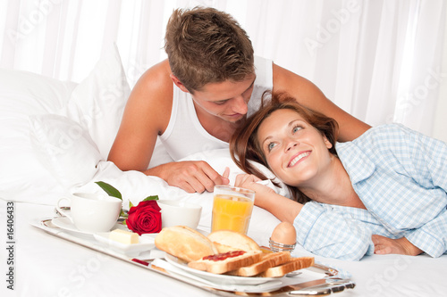 Fototapeta Young smiling couple having luxury breakfast in hotel room obraz