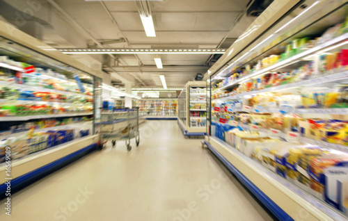 blurred supermarket shelves and aisle with trolley Wallpaper Mural