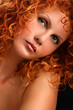 Portrait of beautiful redhead woman with rich curly hair