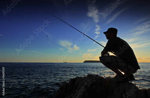Foto op Canvas Vissen Man fishing on sunset