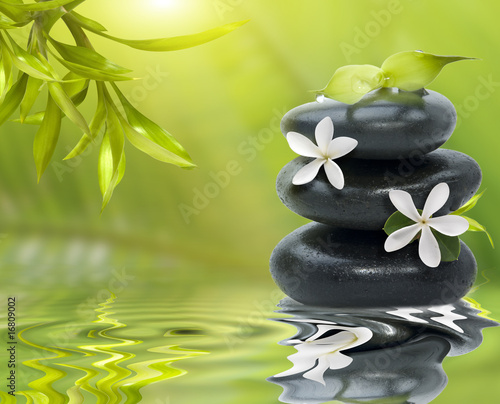 Spa still life, with white flowers on the black stones and bambo