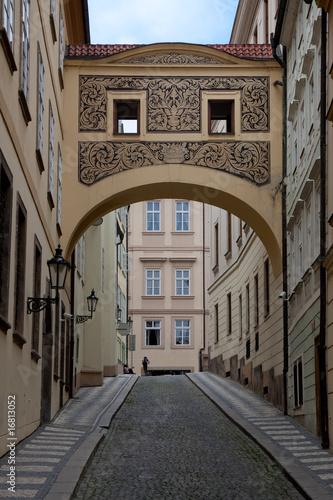 Walkway between buildings in Prague Poster