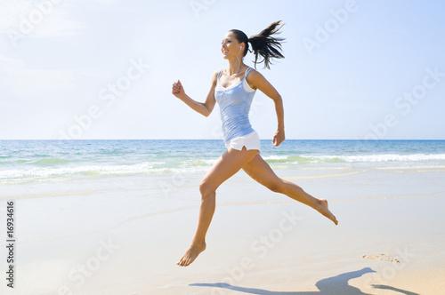 Foto  Junge sportliche Frau rennt am Strand