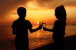 silhouettes of boy and girl with glasses on sea sunset