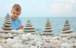 boy and stone stacks on pebble beach