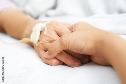 Daughter holding her mother hand in hospital Canvas Print