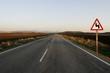 carretera recta con señal de curva peligrosa
