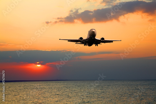 Tuinposter Vliegtuig Silhouette of the big plane on a sunset background