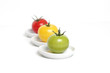 Colorful tomatoes on plates (focus on green)