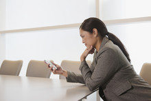 Asian Businesswoman Looking At Electronic Organizer