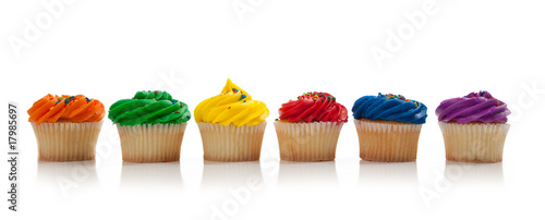 Photo  Assorted colored Cupcakes with sprinkles on white