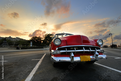 Poster Cubaanse oldtimers Red car in Havana sunset