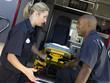 Two paramedics cheerfully removing empty gurney from ambulance