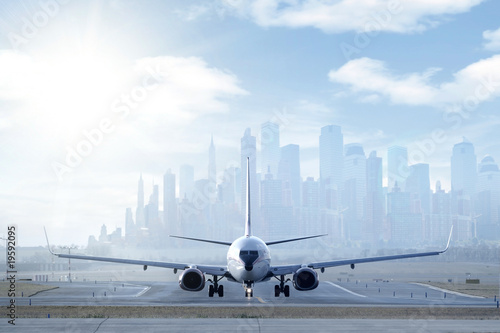Big aircraft on runway in big city Tablou Canvas
