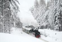 Steam Train Driving Through Snowy Woods