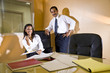 Middle-aged Hispanic businessman and assistant in boardroom