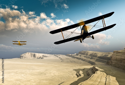 Two vintage WWI double wing biplanes flying over canyon Wallpaper Mural
