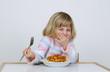 canvas print picture - Kleines Maedchen freut sich ueber Nudeln mit Tomatensauce.