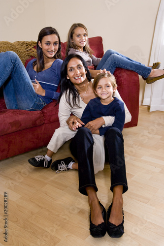 Fotografie, Obraz  Mother and three children sitting at home together on sofa
