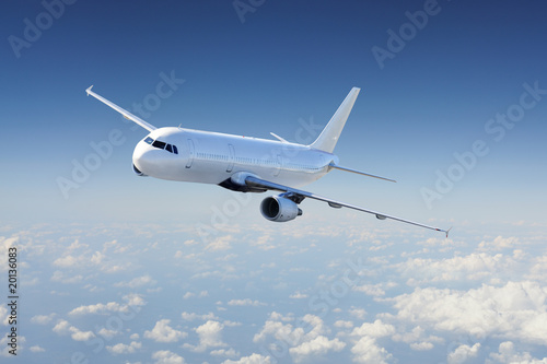 Airplane in the sky, over the cloudy sky Canvas Print