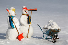 Snowwoman And Snowman With Snow Shovel, Broom And Barrow