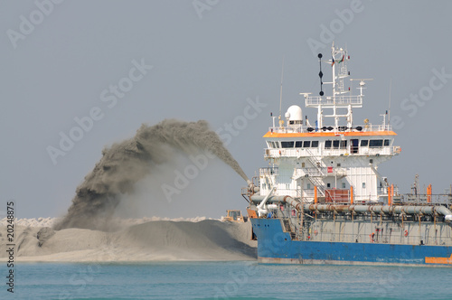 Fényképezés  Dredge ship pipe pushing sand to create new land