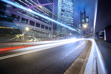 Fototapeta Fast moving cars lights blurred over modern city background
