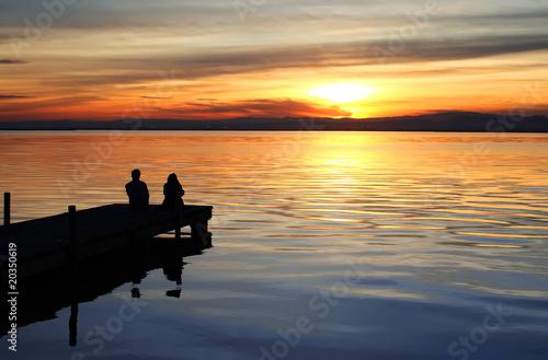 Fototapeten Pier puesta de sol en el lago