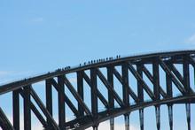 People Walking Across A Bridge