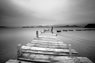 Fototapeta Molo Looking over a pier and boats, black and white