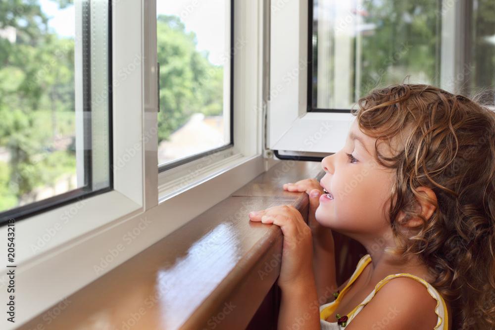 Fototapeta pretty smiling little girl on balcony, look from window