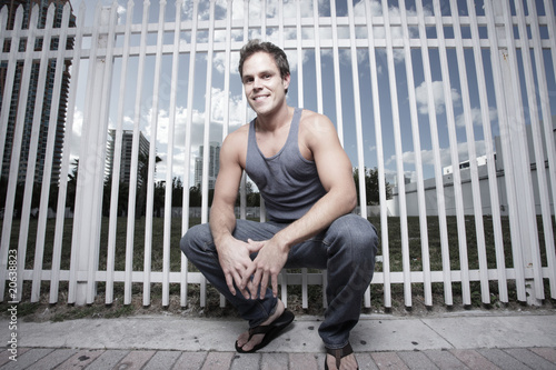 Fototapety, obrazy: Man squatting by a fence